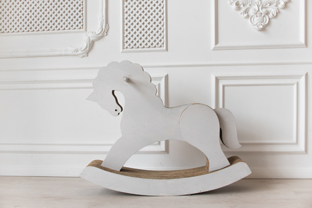 white cardboard horse, childrens toy swinging. interior white wall.