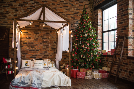 bed with canopy valance baldachin decorated with decorative pillows with a pattern and lamps . Christmas tree with gifts loft style brick wall. new year 2019. Stockfoto