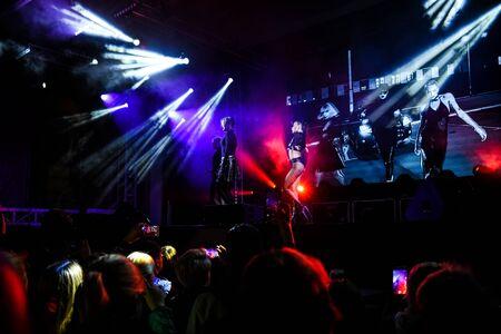 multitud que anima en un concierto, muestra la escena de la gente de neón Editorial