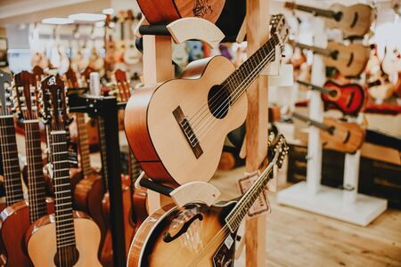 Many colorful wooden guitars put on guitar stand in store showroom. background guitar shop and music shop.