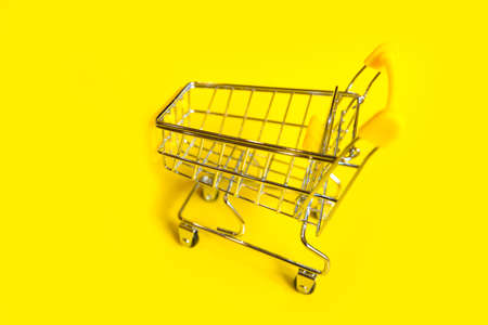 an empty shopping cart on a bright yellow background