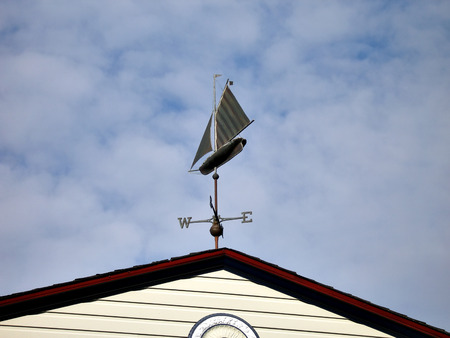 Sailboat wind vane on top of roof against sky