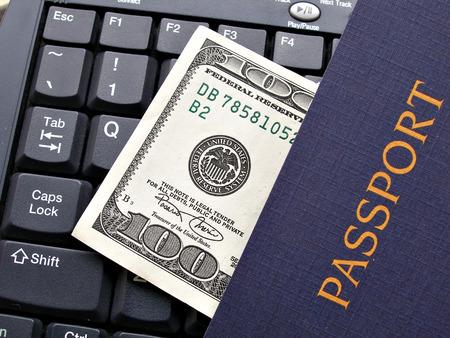 close up shot of hundred dollar bill and passport on keyboard