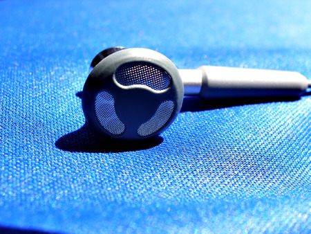close up shot of ear phone on blue sheet Imagens