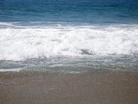 shot of foam as waves crash on shore Imagens