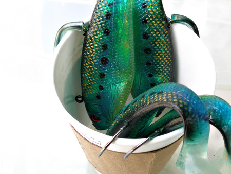 close up shot of green fish lures in coffee cup