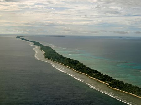 Long winding island covered with trees with shore either side