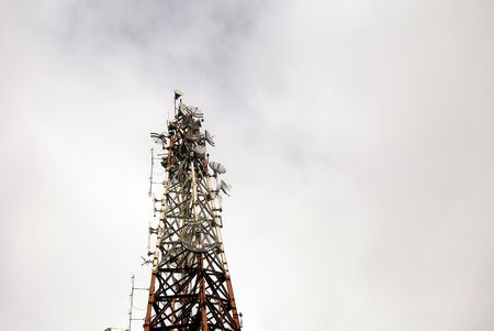 Communications tower against cloudy skies Imagens