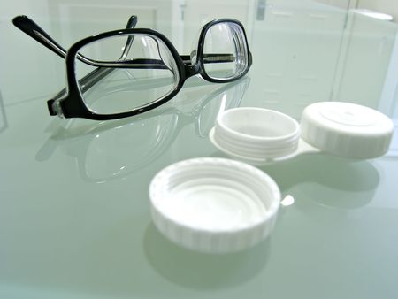 contacting: Close up shot of eyeglasses and contact lens case