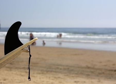 Shot of surfboard with black fin against blurred background of the sea