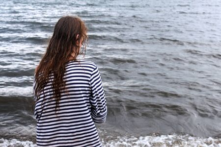Girl on the seashore in a striped T-shirt