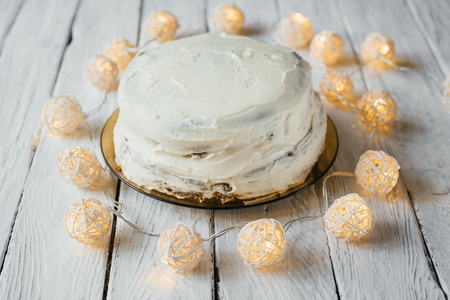 Celebration homemade biscuit cake with white cream on a white wooden table. Twinkling lights around the cake.