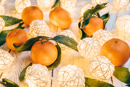 Mandarins with green leaves on a white wooden table. Twinkling lights on a table. Tasty tangerines for the New Year festive table 스톡 콘텐츠