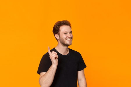 Studio shot of a handsome young man expressing emotion of playful rebuke while standing over orange background. Concept of playful rebuke.