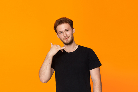Studio shot of a handsome young man pretending to be talking on the phone. while standing over orange background. Concept of communication.