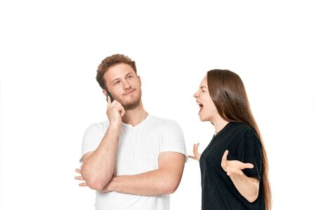 Studio shot of a couple quarreling. Angry woman shouting at the man while he is talking on the phone. Man doesn't pay attention.