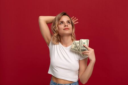 Portrait of a girl with curly blond hair dressed in a white t-shirt standing on a red background. Happy model fans herself with a bundle of dollars with dreamy look. Imagens