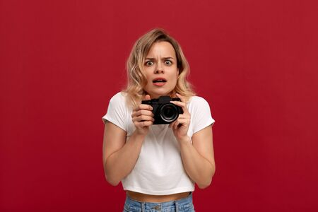 Portrait of a girl with curly blond hair dressed in a white t-shirt standing on a red background. Model with shocked emotions holds retro film camera.