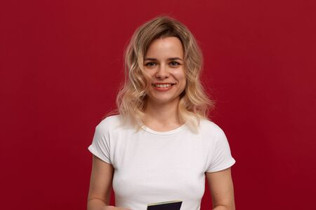 Portrait of a beautiful girl with curly blond hair dressed in a white t-shirt standing on a red background. Model smiles at the camera and holds passport of blue color.
