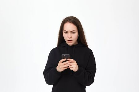 Studio shot of a beautiful young brunette woman with wireless headset looking amazed at the phone while standing over white background. Girl wears black hoodie. Stock Photo
