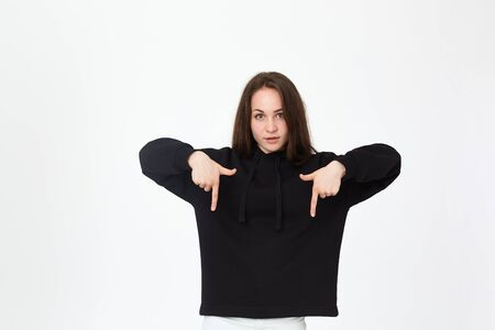 Portrait of a pretty young brunette in a black sweatshirt on a white background pointing down with fingers looking at the camera. Place for advertisement. Stock Photo