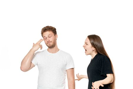 Studio shot of a couple quarreling. Angry woman shouting at the man. Man gets tired of the conflict.
