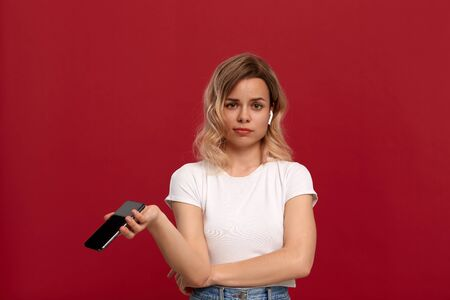 Portrait of a girl with curly blond hair in a white t-shirt on a red background. Unhappy model in wireless headset holds mobile phone. 免版税图像