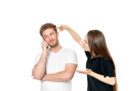 Studio shot of a couple quarreling. Angry woman shouting at the man while he is talking on the phone. Man doesnt pay attention.