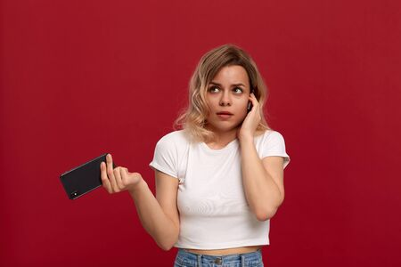 Portrait of a girl with curly blond hair in a white t-shirt on a red background. Uncertain model in wireless headset holds mobile phone.