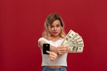 Portrait of a girl with curly blond hair in a white t-shirt standing on a red background. Model with wireless headphones looks at camera showing bank card and a bundle of dollars expressing concern Stock Photo