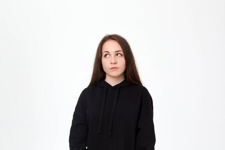 Portrait of a pretty young brunette woman in a black sweatshirt standing infront of white background and looking at the left upper corner. Stok Fotoğraf - 130460589