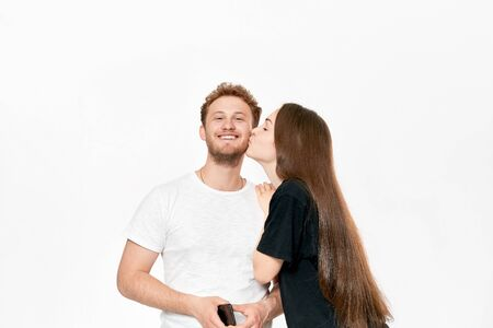 Studio shot of a happy couple kissing. Girlfriend kisses boyfriends cheek. He smiles pleased while standing infront of white background.