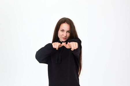 Portrait of a positive beautiful young woman in a black sweatshirt and white pants on a white background pointing at the camera with hands
