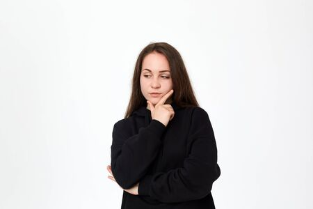 Young beautiful brunette woman looking at the left side with hand raised on chin while standing on a white background. Emotion of interest.