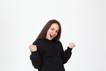 Studio shot of a successful pretty young brunette girl standing over white background. Model shows positive gesture of success at the camera. Concept of success.