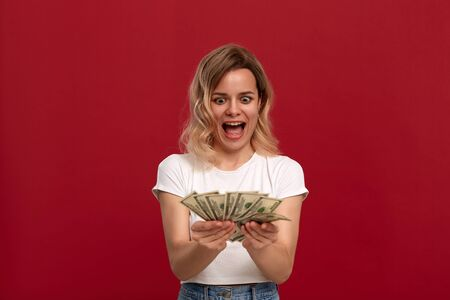 Portrait of a girl with curly blond hair dressed in a white t-shirt standing on a red background. Happy model looks at the bundle of money. Excited girl expresses emotion of surprise Stock Photo