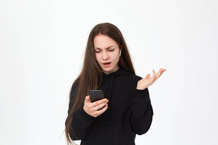 Studio shot of a beautiful young brunette woman with wireless headset who is displeased with what she sees at the screen. Girl expresses skeptical emotion and looks at the camera while standing over white background. Girl wears black hoodie.