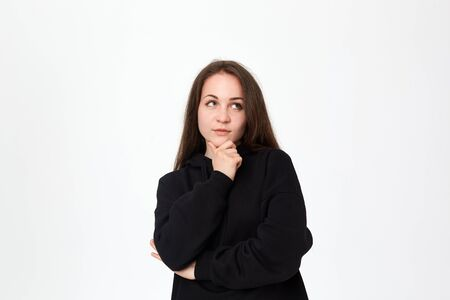 Young beautiful brunette woman looking at the right upper corner with hand raised on chin while standing on a white background. Emotion of interest. Stok Fotoğraf