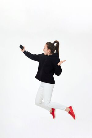 Young pretty brunette girl in black hoodie, white pants and red sneakers making selfie with mobile phone and jumping isolated on white background. Concept of happy active lifestyle.
