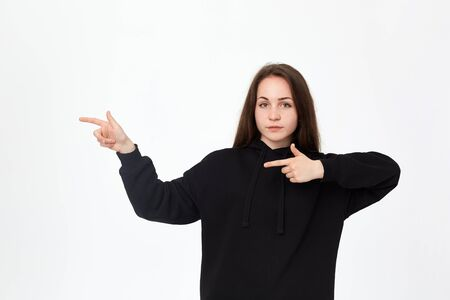 Portrait of a pretty young brunette in a black sweatshirt on a white background pointing with fingers to the left. Place for advertisement.