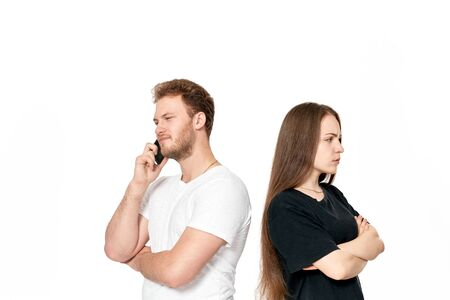 Studio shot of a couple quarreling. Upset woman stands with her back to the boyfriend while he is talking on the phone. Girl holds arms across.