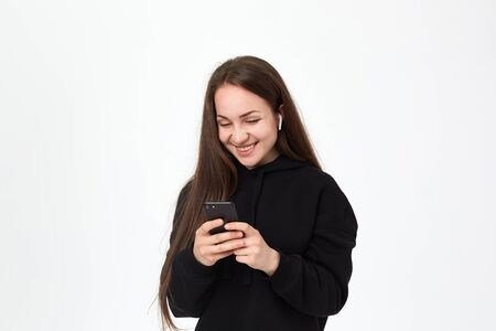 Studio shot of a beautiful young brunette woman with wireless headset smiling looking happy at the phone while standing over white background. Girl wears black hoodie.