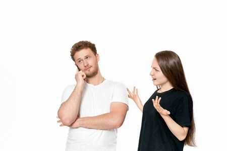 Studio shot of a couple quarreling. Dissatisfied woman looks with suspicion at the man while he is talking on the phone. Man gets tired of the conflict. Girl shrugs her sholders.