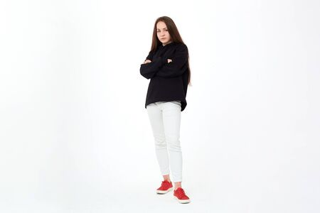 Portrait of a pretty young woman in a black sweatshirt, white pants and red shoes standing infront of white background and keeps arms crossed. Stock Photo