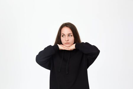 Young beautiful brunette woman smiling and looking up and holding face on hands with cute gesture while standing on a white background. Happy emotion