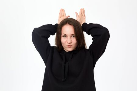 Studio shot of a pretty young brunette woman in a black sweatshirt holding palms of hands like ears of a hare while standing over white background. Concept of having fun.