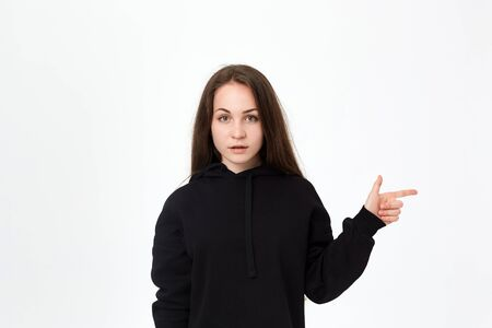Portrait of a pretty young brunette in a black sweatshirt on a white background pointing at the right side with fingers and looking at the camera. Place for advertisement. Stock Photo