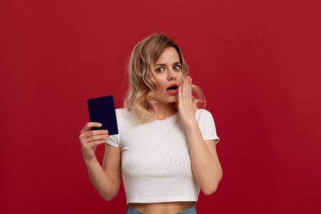 Portrait of a beautiful girl with curly blond hair dressed in a white t-shirt standing on a red background. Model holds passport of blue color and hand raised to the face expressing emotion of surprise