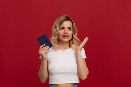Portrait of a beautiful girl with curly blond hair dressed in a white t-shirt standing on a red background. Model with dreamy look holds passport of blue color expressing emotion of dream