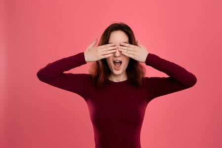 Excited young lady standing isolated over dark pink background keeping palms of hands over her eyes as if she is hiding Stock Photo